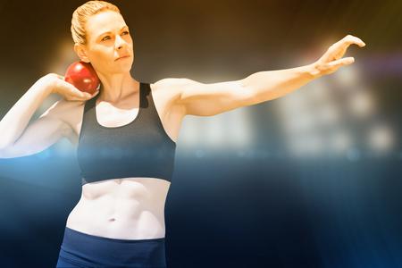 lanzamiento de bala: Vista frontal de la deportista practicando lanzamiento de peso en contra de imagen compuesta de punto de mira
