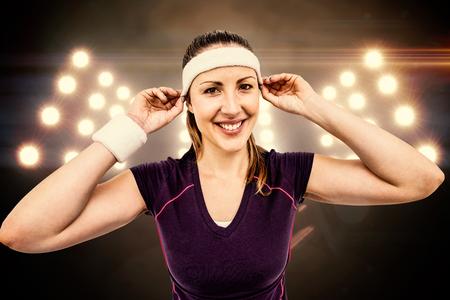 digitally generated image: Female athlete wearing headband and wristband against digitally generated image of spotlight