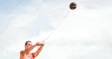 hammer throw: Portrait of sportswoman practising hammer throw  against blue sky with clouds