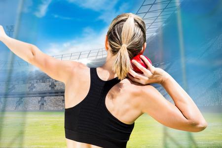 lanzamiento de bala: Vista posterior de la deportista está practicando lanzamiento de peso en contra de vista de un estadio
