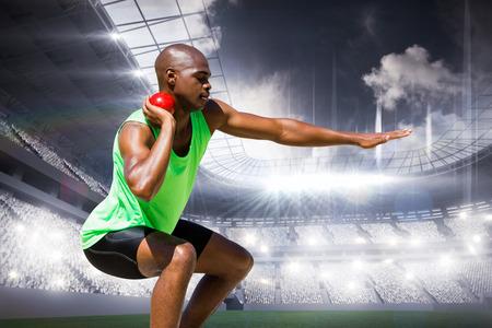 lanzamiento de bala: Deportista practicando el lanzamiento de peso contra la arena deportiva Foto de archivo