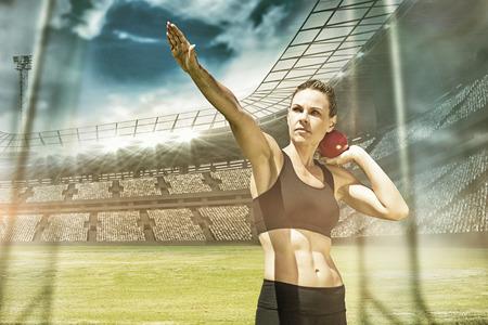 lanzamiento de bala: La deportista practicando el lanzamiento de peso en contra de vista de un estadio Foto de archivo