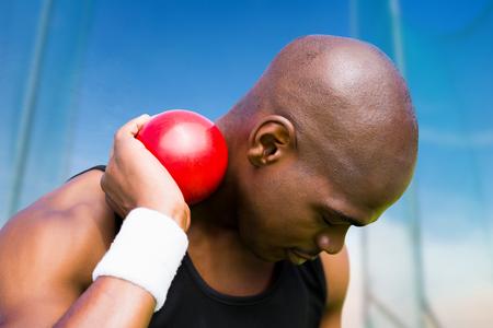 lanzamiento de bala: Retrato de deportista practicando lanzamiento de peso contra la vista panorámica de cielo azul