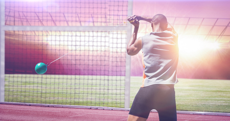hammer throw: Rear view of sportsman practising hammer throw against race track