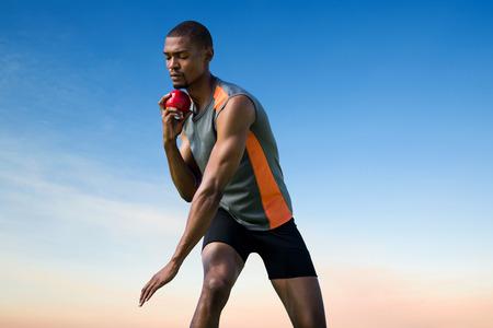 lanzamiento de bala: Athlete man concentrating during his shot put against scenic view of blue sky Foto de archivo