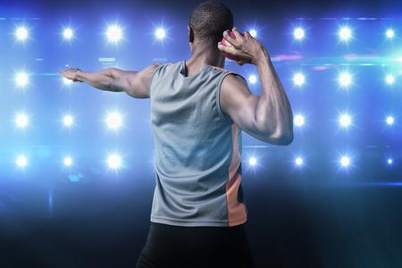 lanzamiento de bala: Vista trasera del hombre atlético preparar el lanzamiento de peso en contra de imagen compuesta de azul foco