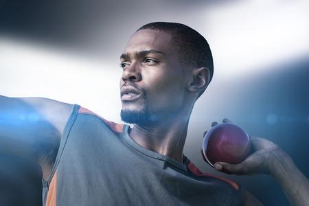 lanzamiento de bala: Retrato de deportista practicando lanzamiento de peso en contra de los proyectores