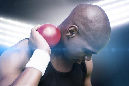 practising: Portrait of sportsman practising shot put  against spotlights Stock Photo