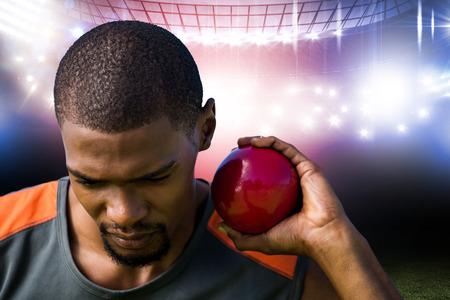 lanzamiento de bala: Portrait of sportsman practising shot put  against american football arena