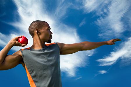 lanzamiento de bala: Vista de perfil de deportista practicando lanzamiento de peso contra el cielo azul con nubes Foto de archivo