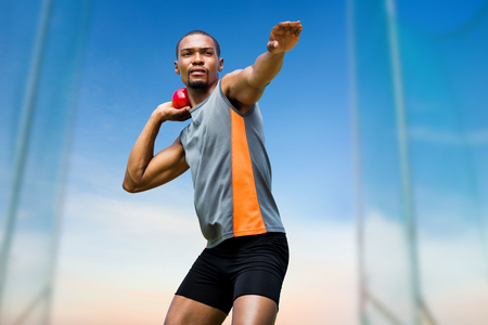 shot put: Front view of sportsman practising shot put  against scenic view of blue sky Stock Photo