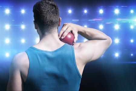 lanzamiento de bala: Vista trasera del deportista practicando lanzamiento de peso en contra de imagen compuesta de azul foco Foto de archivo