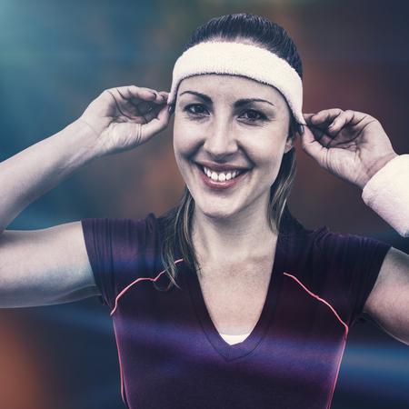 headband: Female athlete wearing headband and wristband against colored background Stock Photo