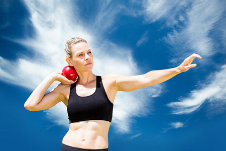 lanzamiento de bala: Vista frontal de la deportista practicando lanzamiento de peso contra el cielo azul con nubes