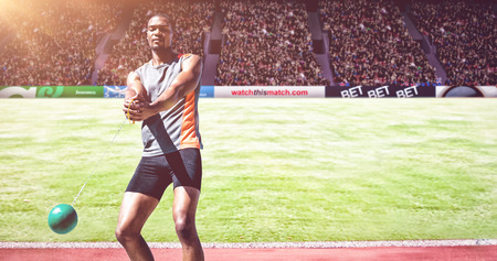 hammer throw: Sporty man playing at hammer throw against athletic field in a stadium Stock Photo