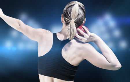 shot put: Rear view of sportswoman is practising shot put  against composite image of spotlight Stock Photo