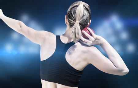 lanzamiento de bala: Vista posterior de la deportista está practicando lanzamiento de peso en contra de imagen compuesta de punto de mira Foto de archivo