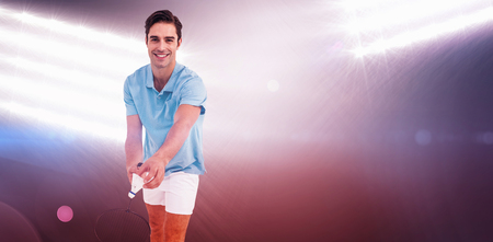 racquet: Badminton player holding a racquet ready to serve against spotlights Stock Photo