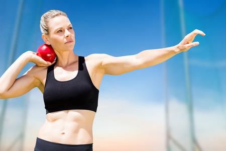 lanzamiento de bala: Vista frontal de la deportista practicando lanzamiento de peso contra la vista panor�mica de cielo azul
