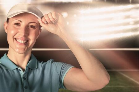 digitally generated image: Sportswoman posing on black background against digitally generated image of tennis court and spotlight