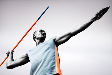 lanzamiento de jabalina: Low angle view of sportsman practising javelin throw  against grey background
