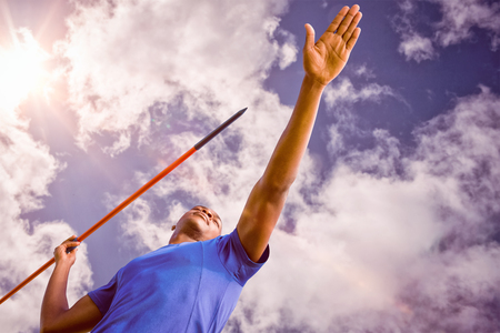 lanzamiento de jabalina: Low angle view of sportsman practising javelin throw  against bright blue sky with clouds Foto de archivo
