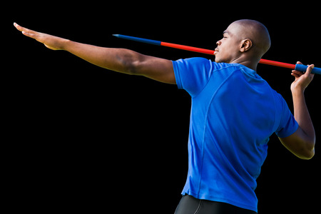 lanzamiento de jabalina: Vista de perfil de deportista practicando tiro de jabalina contra el fondo negro Foto de archivo