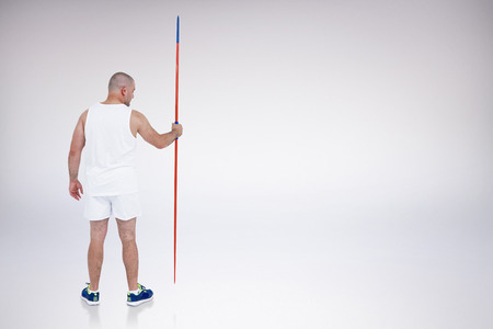 javelin: Athlete standing with javelin against grey background