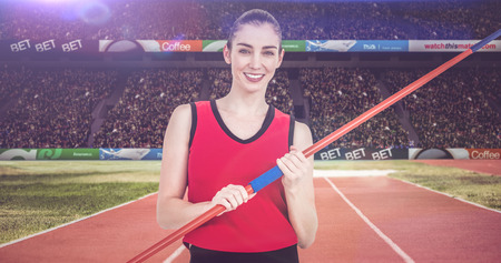 athleticism: Female athlete holding a javelin against athletic field in a stadium
