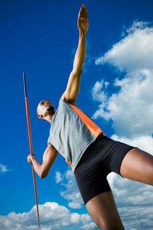 lanzamiento de jabalina: Ángulo de visión baja del hombre atlético preparando su lanzamiento de jabalina contra la opinión de ángulo bajo del cielo azul
