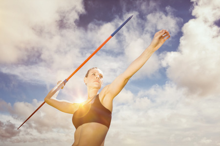 lanzamiento de jabalina: Low angle view of sportswoman is practising javelin throw  against blue sky with white clouds Foto de archivo