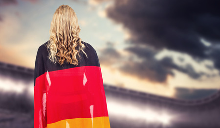 german flag: Athlete with german flag wrapped around her body against composite image of arena and cloudy sky Stock Photo