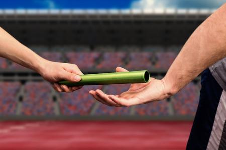 carrera de relevos: El hombre que pasa el testigo al socio en la pista contra el campo de atletismo en un estadio Foto de archivo