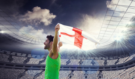 profile view: Profile view of sportsman holding an England flag against rugby stadium