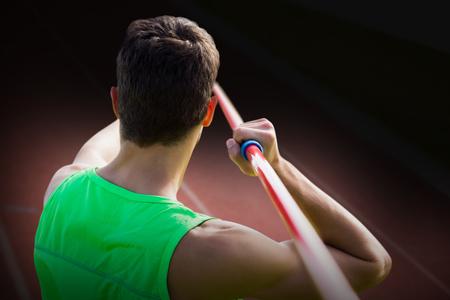 lanzamiento de jabalina: Vista trasera del deportista practicando tiro de jabalina contra el foco en la pista en un día soleado Foto de archivo