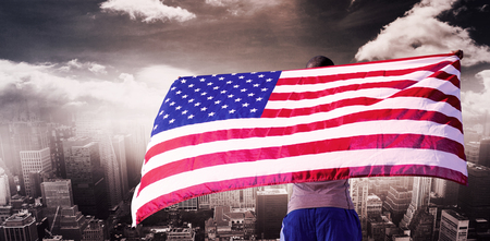 raise the white flag: Rear view of sportsman is raising an american flag  against aerial view of a city on a cloudy day Stock Photo