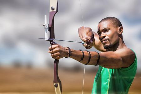 arco y flecha: Cierre de vista de la práctica de tiro con arco hombre contra el paisaje del campo