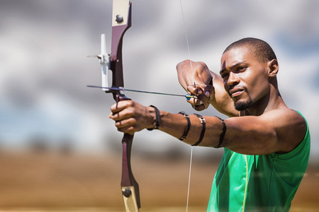 bow and arrow: Close up view of man practicing archery  against landscape of countryside