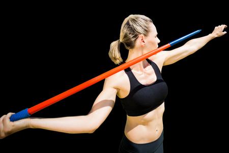 lanzamiento de jabalina: Sportswoman preparing to javelin throw  against black background