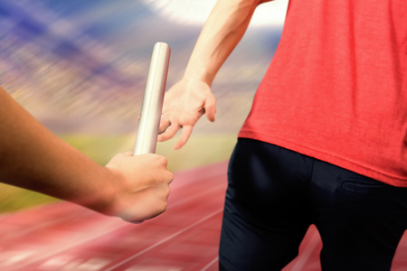 competitive sport: Athlete passing a baton to the partner against athletic track in a stadium