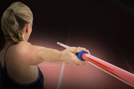 athleticism: Athlete preparing to throw javelin against focus of athletics track