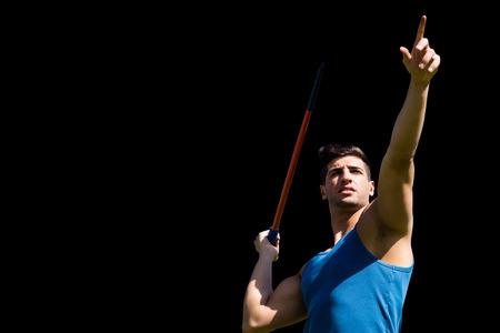lanzamiento de jabalina: Bajo el ángulo de jabalina deportista practicando tiro contra el fondo negro Foto de archivo