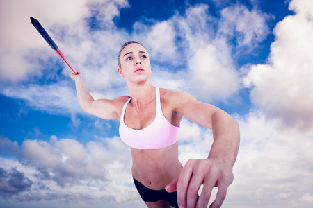 javelin: Female athlete throwing a javelin against blue sky with white clouds