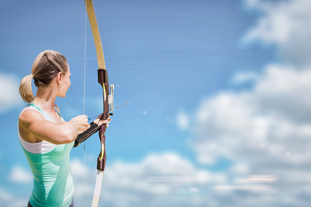 Rear view of sportswoman practising archery  against scenic view of blue sky