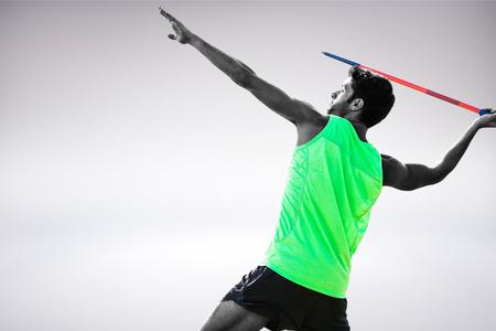 lanzamiento de jabalina: Vista de perfil de deportista practicando tiro de jabalina contra el fondo gris Foto de archivo