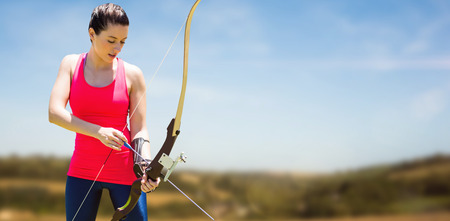 Athletic woman practicing archery against blue sky over fields