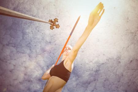 lanzamiento de jabalina: Mujer deportiva que prepara su lanzamiento de jabalina contra el ángulo de visión baja de reflector