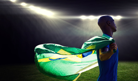 profile view: Profile view of sportsman holding a Brazilian flag  against rugby stadium Stock Photo
