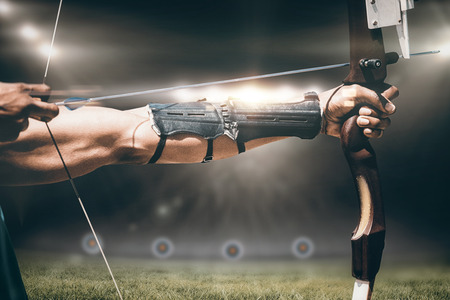 Close up of man stretching his bow on a sports field