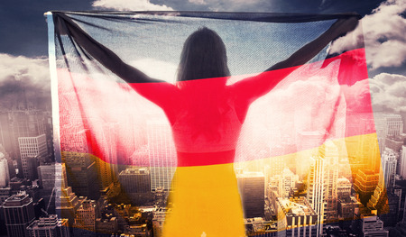 sunshines: Athlete posing with german flag after victory against aerial view of a city on a cloudy day